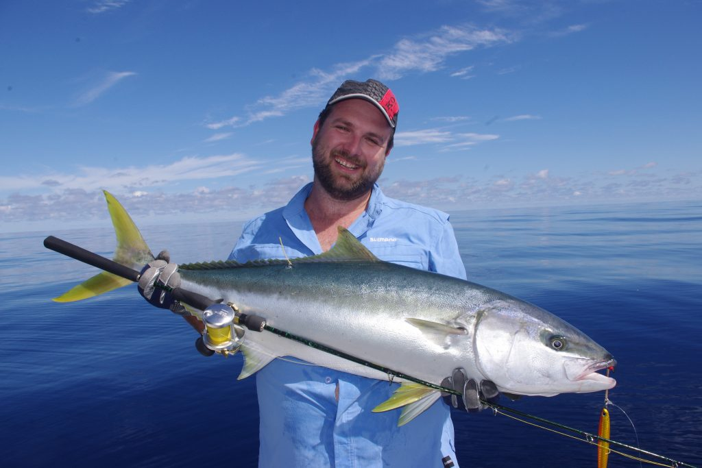 Man holding yellowtail kingfish